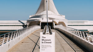 The entrance walkway to a museum with a sign displayed announcing the museum's closure.